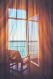 Δωμάτιο ξενοδοχείου με ένα σπίτι άποψης θάλασσας κοντά στη θάλασσα στην περιβαλλοντική θέση στο νησί Το παράθυρο που αγνοεί τον ω Στοκ Φωτογραφία