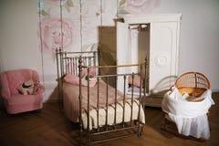 Δωμάτιο παιδιών ` s με μια άσπρη ντουλάπα, υφαμένο κρεβάτι μετάλλων Στοκ Φωτογραφίες