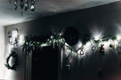 Δωμάτιο το βράδυ που διακοσμείται με το στεφάνι Χριστουγέννων και τα φω'τα και το γ Στοκ Εικόνες
