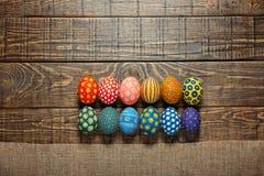 Δωδεκάα ζωηρόχρωμα χρωματισμένα αυγά Πάσχας στο ξύλινο υπόβαθρο Στοκ εικόνες με δικαίωμα ελεύθερης χρήσης