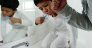 Δόντια βουρτσίσματος πατέρων και γιων στο λουτρό απόθεμα βίντεο
