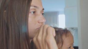 Δόντια οικογενειακού βουρτσίσματος με μια οδοντόβουρτσα στο λουτρό απόθεμα βίντεο