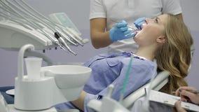 Δόντια της όμορφης γυναίκας που εξετάζουν στην οδοντική κλινική φιλμ μικρού μήκους