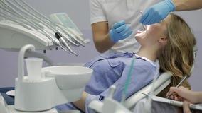 Δόντια της όμορφης γυναίκας που εξετάζουν στην οδοντική κλινική απόθεμα βίντεο