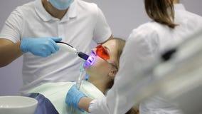 Δόντια της όμορφης γυναίκας που λευκαίνουν στην οδοντική κλινική απόθεμα βίντεο