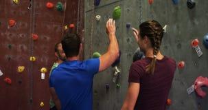 Δόσιμο ανδρών και γυναικών υψηλός-πέντε αναρριμένος σε έναν τεχνητό τοίχο 4k απόθεμα βίντεο