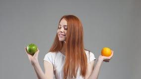 Δόσιμο προτεραιότητας στο πράσινο μήλο Το όμορφο κορίτσι επιλέγει μεταξύ του πορτοκαλιού ή του μήλου απόθεμα βίντεο