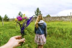 Δόσιμο της αρκετά χειροποίητης ανθοδέσμης λουλουδιών σε ένα κορίτσι Στοκ Φωτογραφίες