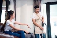 Δύναμη φίλων που διατάζει το φίλο για να κάνει την οικιακή εργασία από το vacu στοκ φωτογραφία με δικαίωμα ελεύθερης χρήσης