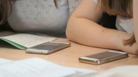 Δύο άγνωστα κορίτσια σπουδαστών με τα smartphones φιλμ μικρού μήκους
