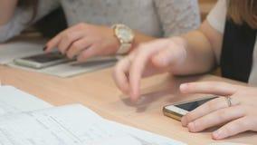 Δύο άγνωστα κορίτσια σπουδαστών με τα smartphones απόθεμα βίντεο