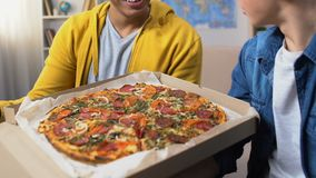 Δύο άνδρες σπουδαστές που ανοίγουν το κιβώτιο πιτσών και που εξετάζουν νόστιμο το γεύμα, γρήγορο γεύμα απόθεμα βίντεο