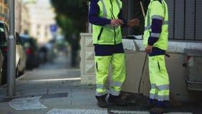 Δύο άνδρες υπάλληλοι της δημοτικής υπηρεσίας πόλεων που επικοινωνεί κατά τη διάρκεια του σπασίματος, εργασία φιλμ μικρού μήκους
