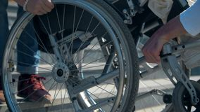 Δύο άνδρες φέρνουν μια γυναίκα σε μια αναπηρική καρέκλα στα βήματα που τα στενά επάνω χέρια των δύο ανδρών φέρνουν μια γυναίκα σε απόθεμα βίντεο