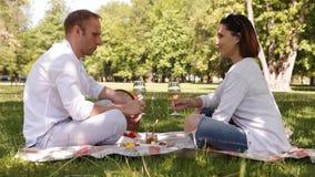 Δύο άνθρωποι έχουν μια ρομαντική ημέρα σε ένα πάρκο πίνοντας το άσπρο κρασί φιλμ μικρού μήκους