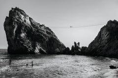 Δύο άνθρωποι περπατούν κατά μήκος μιας γέφυρας σχοινιών στην κορυφή ενός απότομου βράχου επάνω από τη θάλασσα bw, τονισμός Στοκ Εικόνες