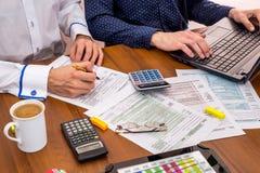 δύο άνθρωποι που γεμίζουν τις φορολογικές μορφές Στοκ φωτογραφίες με δικαίωμα ελεύθερης χρήσης