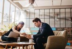Δύο άνθρωποι που κάθονται στο γραφείο πιέζουν τη χρησιμοποίηση του κινητού τηλεφώνου Στοκ φωτογραφία με δικαίωμα ελεύθερης χρήσης