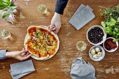 Δύο άνθρωποι που μοιράζονται την πρόσφατα γίνοντη χορτοφάγο πίτσα στοκ εικόνες με δικαίωμα ελεύθερης χρήσης