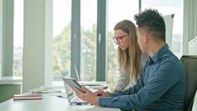 Δύο άνθρωποι που συζητούν τις ιδέες που χρησιμοποιούν την ψηφιακή ταμπλέτα απόθεμα βίντεο