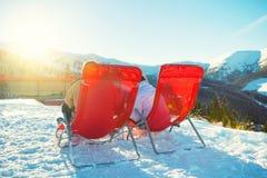 Δύο άνθρωποι που χαλαρώνουν στις καρέκλες apres πλησίον κάνουν σκι φραγμός σε Chopok προς τα κάτω σε Jasna - τη Σλοβακία Στοκ Φωτογραφίες