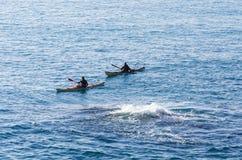 Δύο άνθρωποι σε ένα καγιάκ στη θάλασσα κοντά σε μια δίνη Στοκ Εικόνες