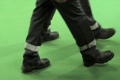 Δύο άνθρωποι στις φόρμες στα μαύρα παπούτσια πηγαίνουν σε ένα πράσινο υπόβαθρο Πόδια των μεγάλων ατόμων στις μπότες ενός εργαζομέ στοκ φωτογραφία