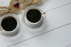 Δύο άσπρα και χρυσά φλιτζάνια του καφέ με τους διακοσμητικούς χρυσούς κλάδους και μικρή κόκκινης καρδιά γυαλιού και στο άσπρο ξύλ Στοκ φωτογραφία με δικαίωμα ελεύθερης χρήσης