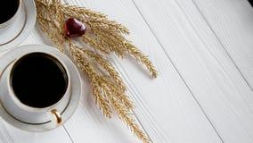 Δύο άσπρα και χρυσά φλιτζάνια του καφέ με τους διακοσμητικούς χρυσούς κλάδους και μικρές καρδιές γυαλιού στο άσπρο ξύλινο υπόβαθρ Στοκ Εικόνες