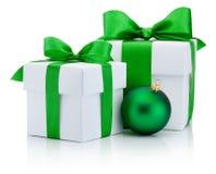 Δύο άσπρα κιβώτια έδεσαν το πράσινες τόξο κορδελλών σατέν και τη σφαίρα Χριστουγέννων Στοκ Εικόνες