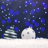 Δύο άσπρα μπιχλιμπίδια Χριστουγέννων γυαλιού με το bokeh στοκ εικόνες