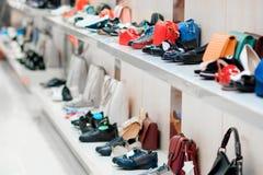 Δύο άσπρα ράφια μαγαζιό με τις πολύχρωμα τσάντες και τα παπούτσια στοκ εικόνες