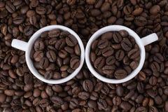 Δύο άσπρα φλυτζάνια με τα φασόλια καφέ Στοκ φωτογραφία με δικαίωμα ελεύθερης χρήσης