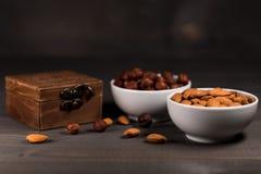 Δύο άσπρα φλυτζάνια που γεμίζουν με τα καρύδια, τα αμύγδαλα και τα φουντούκια και μια ξύλινη κασετίνα Στοκ Εικόνες