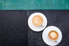 Δύο άσπρα φλυτζάνια του νόστιμου cappucino με την τέχνη latte στην άκρη της πισίνας στοκ εικόνες