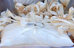 Δύο άσπρα χρυσά γαμήλια δαχτυλίδια στο άσπρο μαξιλάρι δαντελλών και το μπεζ τόξο Στοκ Φωτογραφία