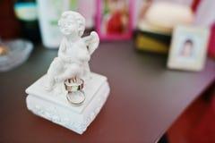 Δύο άσπρα χρυσά γαμήλια δαχτυλίδια στο ειδώλιο αγγέλου Στοκ φωτογραφία με δικαίωμα ελεύθερης χρήσης