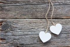 Δύο άσπρες καρδιές στην παλαιά ξύλινη επιφάνεια στοκ εικόνες