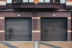 Δύο άσπρες πόρτες γκαράζ για το χώρο στάθμευσης στο κατοικημένο σπίτι Στοκ Φωτογραφία