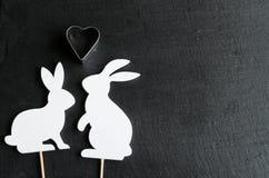 Δύο άσπρες σκιαγραφίες λαγουδάκι ερωτευμένες στο φυσικό μαύρο υπόβαθρο στοκ εικόνες