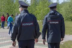 Δύο άτομα αστυνομίας σε ομοιόμορφο πηγαίνουν στη θέση όπου οι διακοπές, οπισθοσκόπες στοκ φωτογραφία