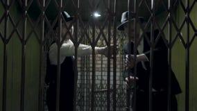 Δύο άτομα γκάγκστερ στα επίσημα κοστούμια και το καπέλο fedora που ανοίγουν ένα μέταλλο σφυρηλάτησαν τις πύλες απόθεμα βίντεο