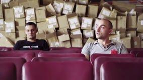 Δύο άτομα κάθονται στη σειρά των πορφυρών καρεκλών με το μεγάλο σωρό τ απόθεμα βίντεο