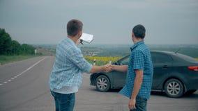 Δύο άτομα κάνουν τη διαπραγμάτευση Αγοράζοντας ή νοικιάστε ένα αυτοκίνητο πώληση ασφαλείας αυτοκινήτου της χρησιμοποιημένης έννοι φιλμ μικρού μήκους