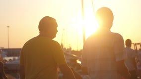 Δύο άτομα περπατούν στον περίπατο Όμορφο ηλιοβασίλεμα στην παραλία γιοτ κίνηση αργή 1920x1080 απόθεμα βίντεο
