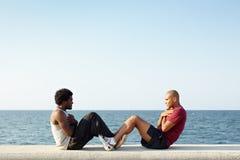 Δύο άτομα που ασκούν τα ABS κοντά στη θάλασσα Στοκ Εικόνες