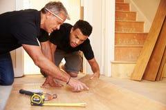 Δύο άτομα που βάζουν το ξύλινο δάπεδο επιτροπής σε ένα σπίτι στοκ εικόνες