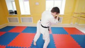 Δύο άτομα που εκπαιδεύουν τις δεξιότητες aikido τους στο στούντιο Χτύπημα του αντιπάλου στο βραχίονα και ρίψη τον στο πάτωμα φιλμ μικρού μήκους