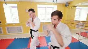 Δύο άτομα που εκπαιδεύουν τις δεξιότητες aikido τους στο στούντιο Κατάρτιση των fistfights τους Χτύπημα του αέρα με τις πυγμές το φιλμ μικρού μήκους