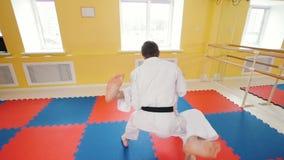 Δύο άτομα που εκπαιδεύουν τις δεξιότητες aikido τους στο στούντιο Κατάρτιση της πάλης τους Προστασία από ένα χτύπημα ποδιών απόθεμα βίντεο